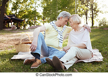 Cheerful pensioners sharing love in the park
