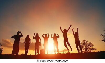 Cheerful People Jumping at Sunset