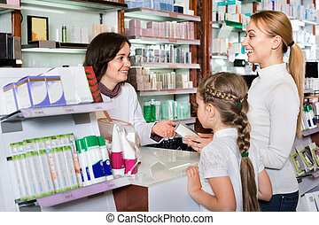 Cheerful pharmacist the pharmaceutical store and consulting customers
