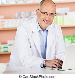 Cheerful pharmacist with laptop - Cheerful pharmacist ...