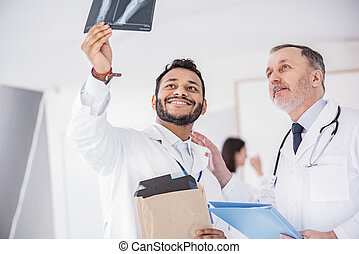Cheerful physicians watching at image in hospital