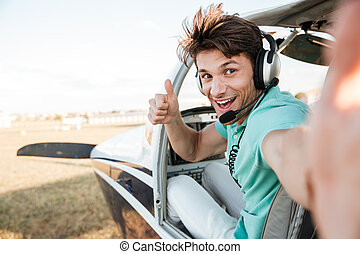 Cheerful pilot sitting in airplane cabin and showing thumbs...