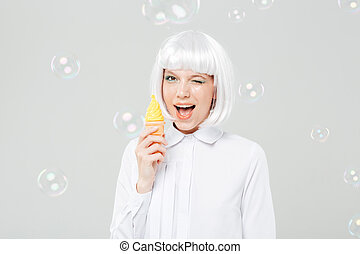 Cheerful playful young woman winking and holding fake ice cream