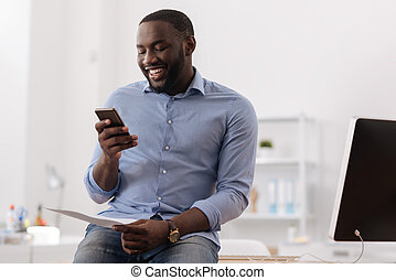 Cheerful pleasant man holding his smartphone