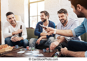 Cheerful pleasant men playing the poker game - True...