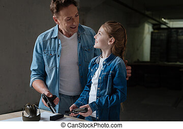 Cheerful positive father looking at his daughter