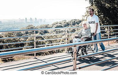 Cheerful positive man pulling a wheelchair