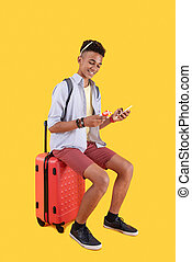 Cheerful positive man sitting on a suitcase