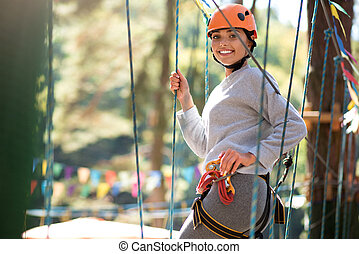 Cheerful positive woman having a great time in adventure park