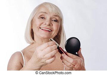 Cheerful positive woman putting on mascara