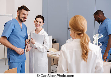 Cheerful practitioners taking part in medical conference at work
