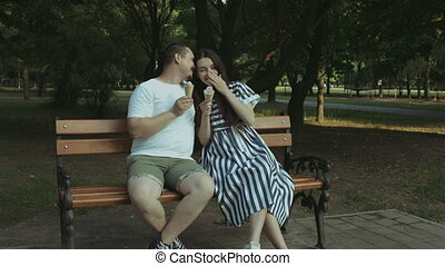 Cheerful pregnant couple eating ice cream in park