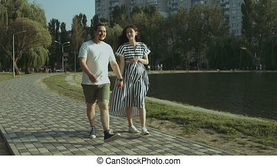 Cheerful pregnant couple walking along lake in park