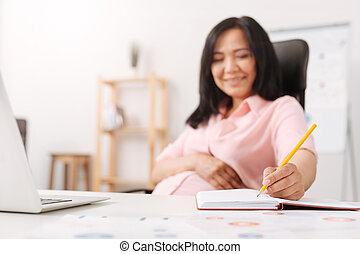 Cheerful pregnant woman making notes in the office