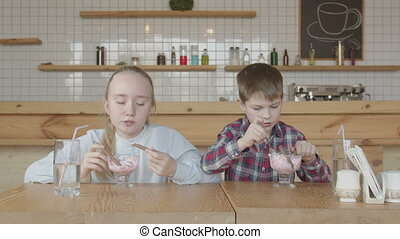 Cheerful preteen kids eating ice cream in cafe