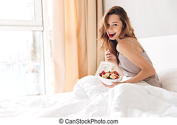 Cheerful pretty lady sitting on bed indoors eating fruit...