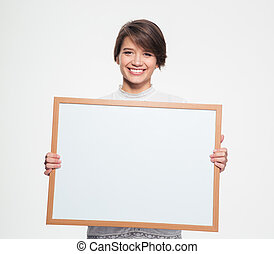 Cheerful pretty woman holding blank board in front of...