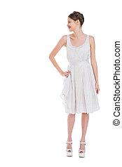Cheerful pretty woman in white dress posing