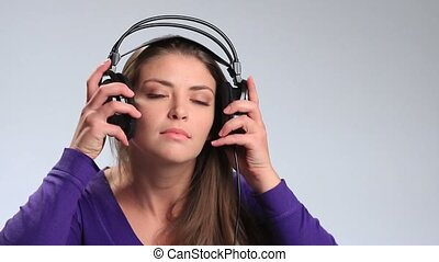 Cheerful pretty woman listening music in headphones