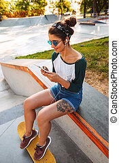 Cheerful pretty woman sitting outdoors with skateboard