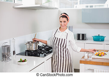 Cheerful pretty woman with apron cooking