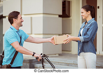Cheerful professional courier delivering parcel to the client