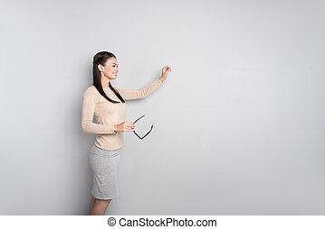 Cheerful professional female teacher standing near board