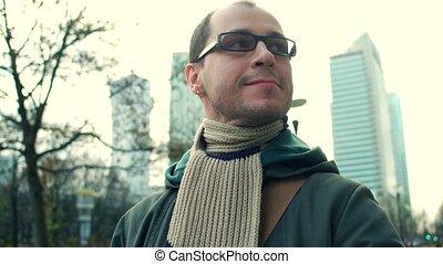 Cheerful programmer wearing black rim glasses walks on city...
