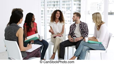 Cheerful psychologist leading group of people in group...