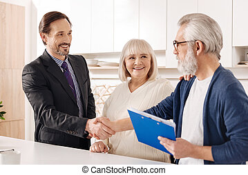Cheerful real estate agent presenting contract to elderly couple