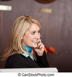 cheerful receptionist using telephone