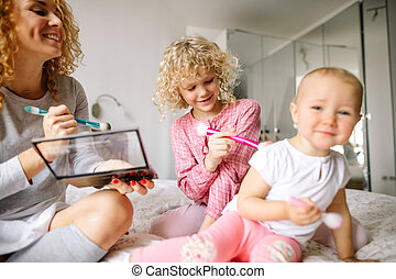 cheerful red-haired woman and her daughter tickling the baby...