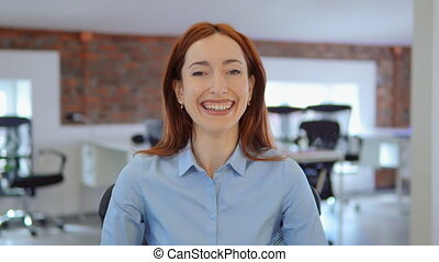 cheerful redhead businesswoman smiling at work - employee...