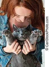 cheerful redhead girl plays with her blue cat