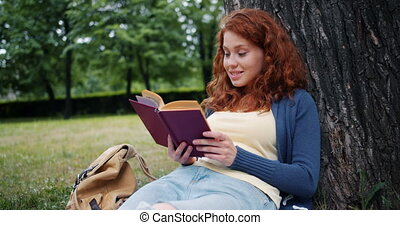 Cheerful redhead girl reading book outdoors in park smiling...