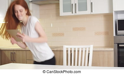 Cheerful redhead girl uses tablet at home in kitchen. -...