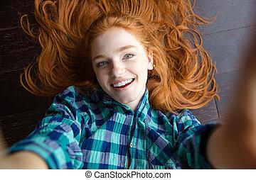 Cheerful redhead woman making self image lying on the floor