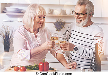 Cheerful retired couple drinkign white wine in the kitchen