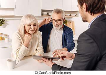 Cheerful retired couple using gadget with real estate agent