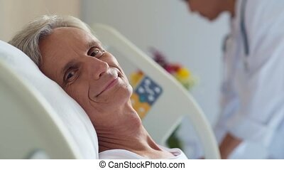 Cheerful retired man lying in a hospital bed