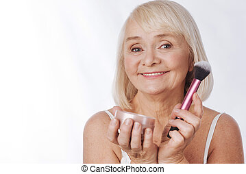 Cheerful retired woman making using face powder