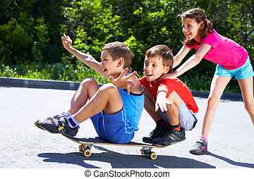 Cheerful ride - A girl pushing skateboard with two boys ...