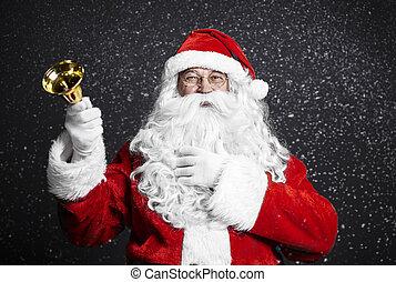 Cheerful santa claus holding handbell