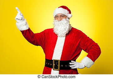 Cheerful Santa pointing away. Copy space concept.