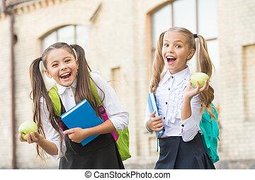 Cheerful schoolgirls enjoying healthy school lunch, knowledge day concept.