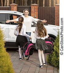 Cheerful schoolgirls running to mother meeting them after school