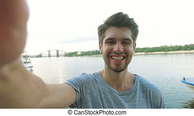 Cheerful selfie. Cheerful young man in shirt holding mobile phone and making photo of himself while standing in city river