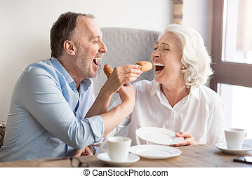 Cheerful senior couple eating croissant