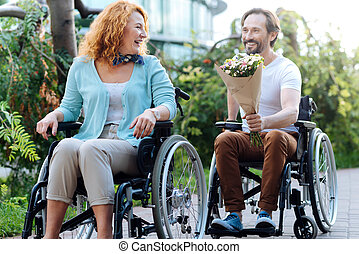 Cheerful senior couple having a wlak in the wheelchairs