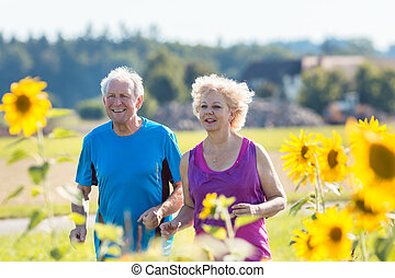 Cheerful senior couple jogging together outdoors in the countrys